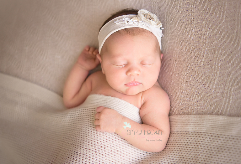 Newborn baby girl in a cream headband