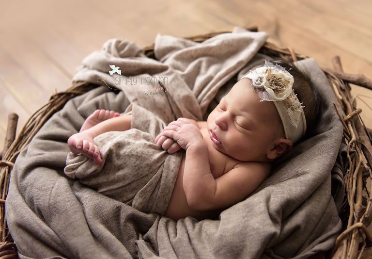 newborn baby girl with a white headband swaddled in a nest layed on the ground