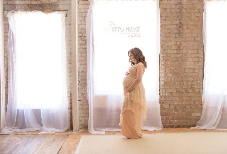 pregnant woman standing in front of a window during a maternity portrait session wearing a dress